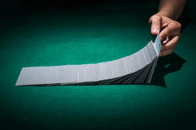 Hand, die pokerkarte auf kasinotabelle hält