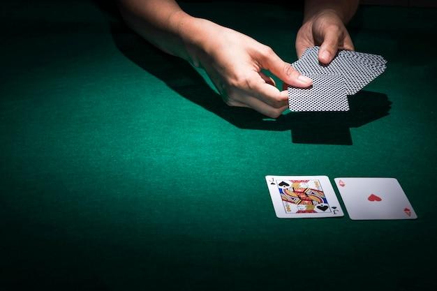 Hand, die pokerkarten auf kasinotabelle hält