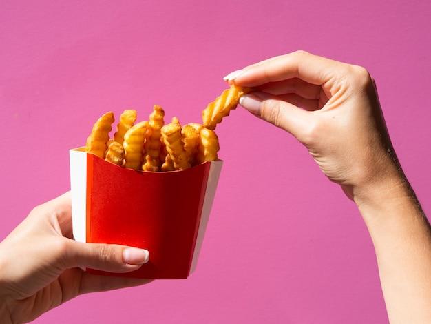 Hand, die pommes-frites auf rosa hintergrund auswählt