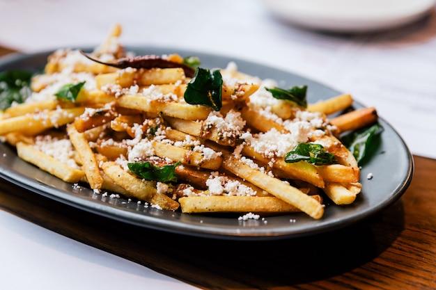Hand, die pommes-frites mit gebratenem basilikum klemmt