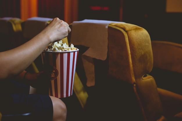 Hand, die popcorn aus dem popcorn-eimer in einem kino pflückt.