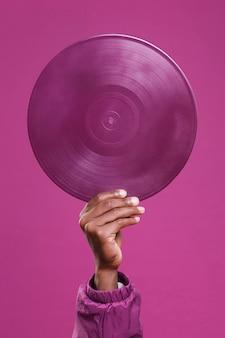 Hand, die purpurrotes vinyl hält