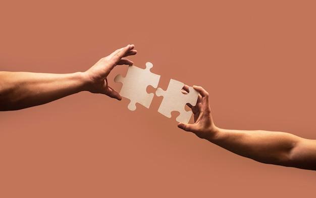 Hand, die puzzle verbindet. geschäftslösungen, erfolg und strategiekonzept. mannhände verbinden paar puzzleteile. geschäftslösungen, ziel, erfolg, ziele und strategiekonzepte.