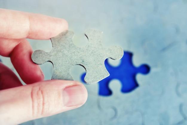Hand, die puzzleteil mit dem letzten fehlenden stück hält.