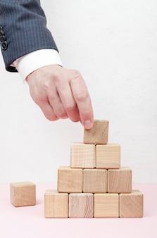 Hand, die pyramide aus holzwürfeln schafft