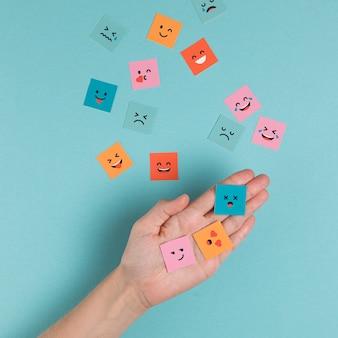 Hand, die quadratische lächelnde gesichter hält