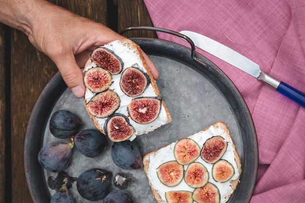 Hand, die ricotta-sandwich mit frischen feigen isst