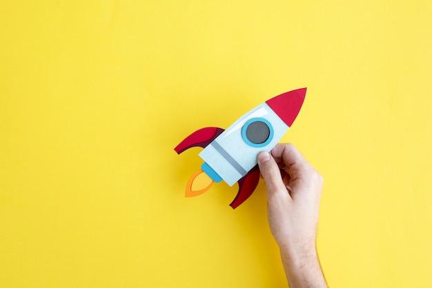 Hand, die rocket spaceship auf gelbem hintergrund hält