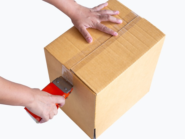 Hand, die rolle des klaren plastikverpackungsbandes und des braunen kastens lokalisiert auf weißem hintergrund hält.