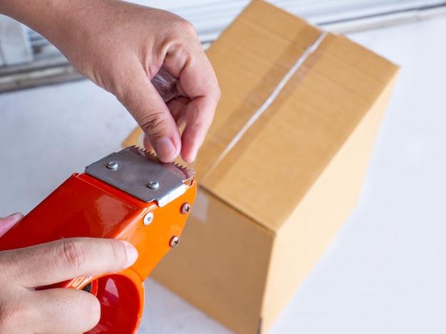 Hand, die rolle des klaren plastikverpackungsbands hält