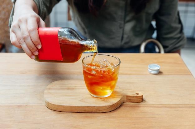 Hand, die roten aufkleber kalten gebräu-tee in trinkglas mit eis gießt.