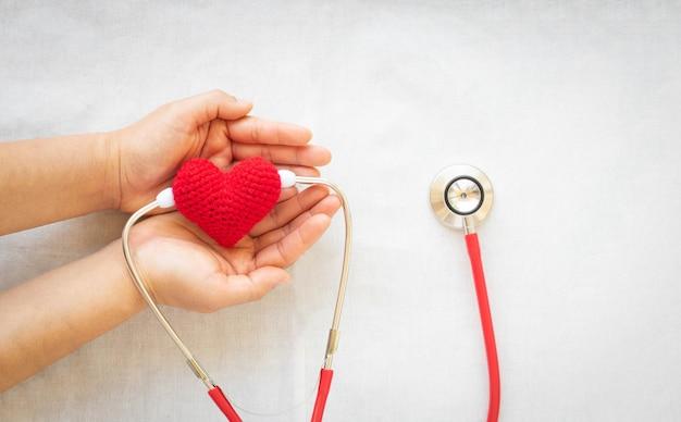 Hand, die rotes herz und stethoskop hält. herzgesundheit, kardiologie, organspende, weltherztag.