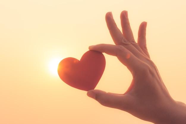 Hand, die rotes herz während des sonnenunterganghintergrundes hält. liebe, valentinstag-konzept