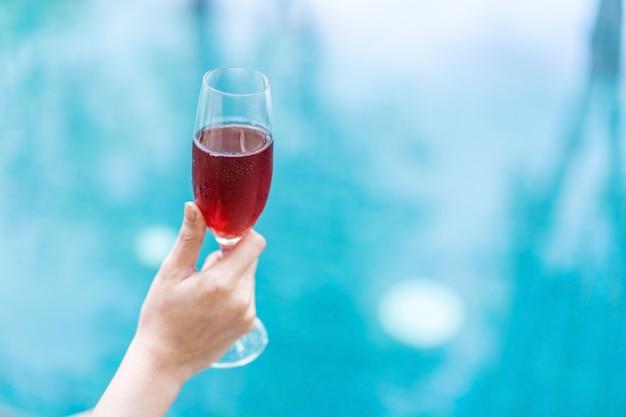 Hand, die rotweinglas im pool hält