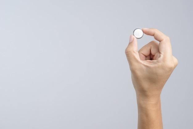 Hand, die runde lithiumknopfzellenbatterie hält