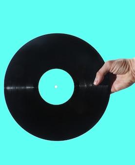 Hand, die schallplatte lokalisiert auf blauem retro-stil hält
