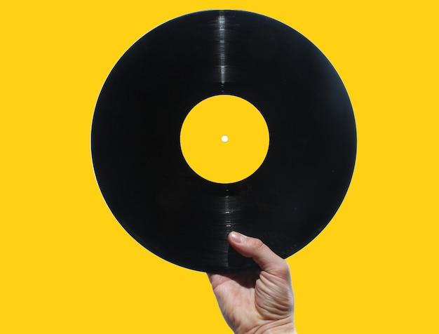 Hand, die schallplatte lokalisiert auf gelbem retro-stil hält