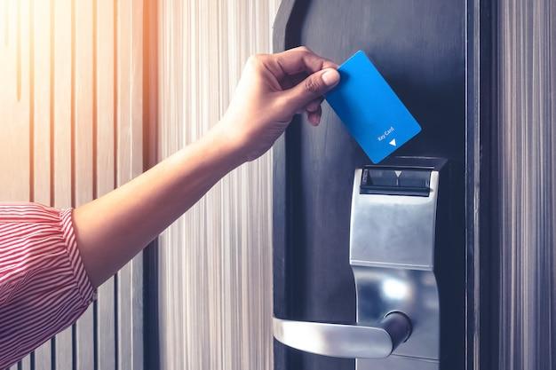 Hand, die schlüsselkarte einfügt, um eine türsicherheitsauthentifizierung im hotel- oder wohnungsschutz aufzuheben