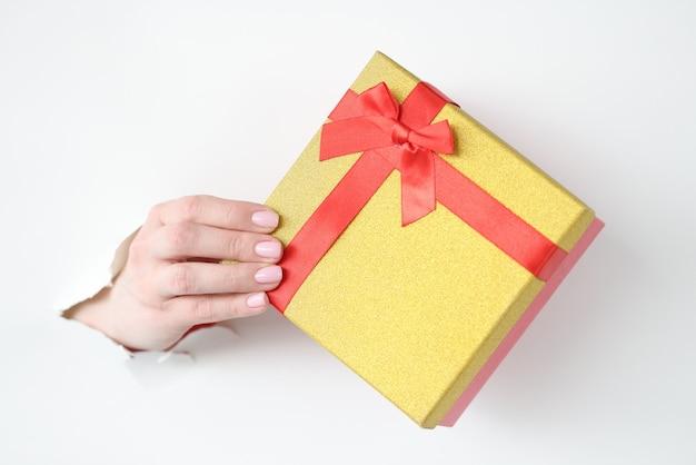 Hand, die schönes geschenk aus zerrissenem papier herauszieht