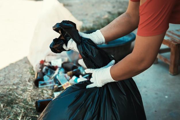 Hand, die schwarze abfalltasche hält