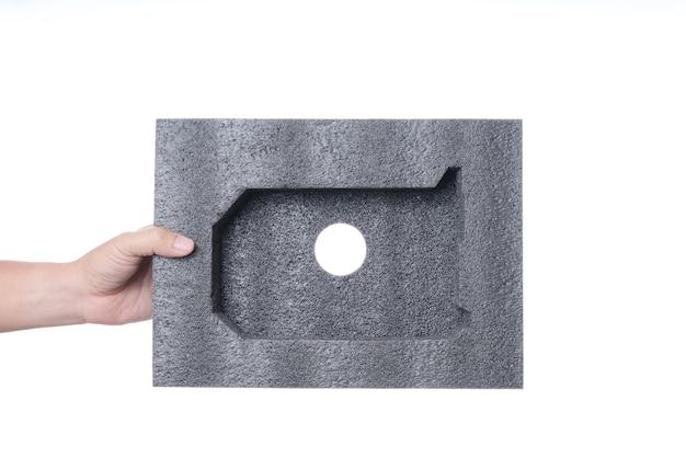 Hand, die schwarzen schwammschaum in einer form des elektronischen oder computerteils hält