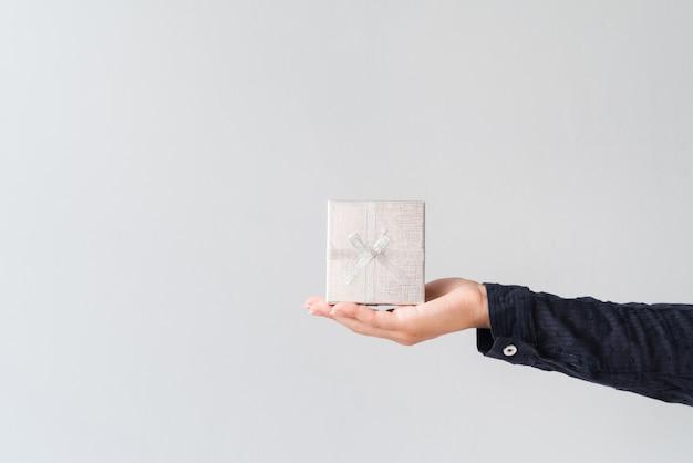 Hand, die silber eingewickeltes geschenk hält Kostenlose Fotos