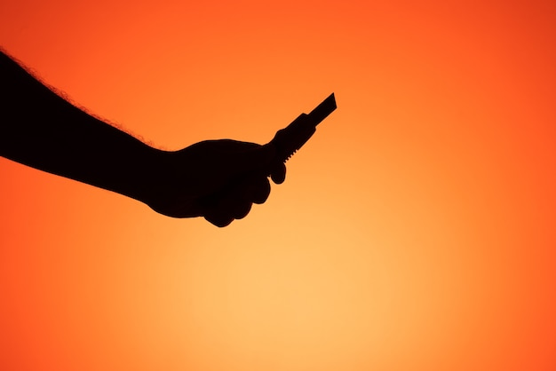 Hand, die skalpell auf orangem hintergrund hält. silhouettenfotografie