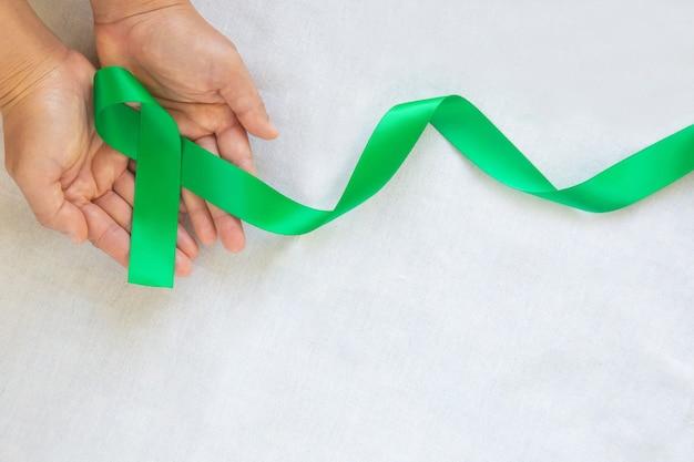 Hand, die smaragdgrünes lockiges band auf weißer stoffoberfläche hält
