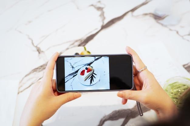 Hand, die smartphone hält, das ein foto des nachtischs nimmt.
