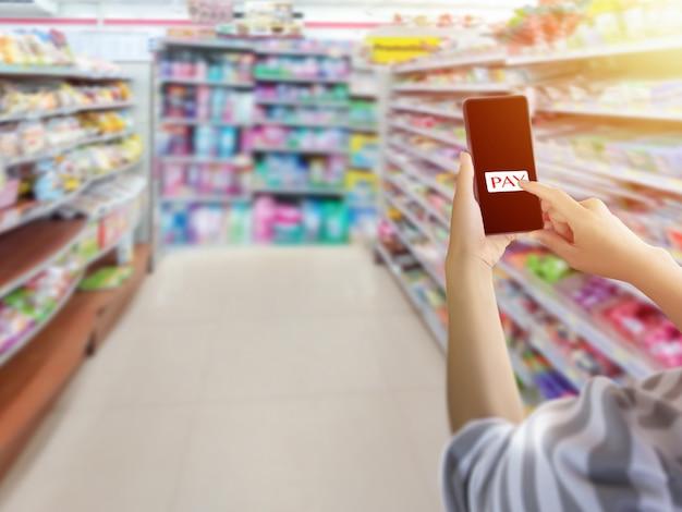 Hand, die smartphone hält und den index feiner zeigt, um die schaltfläche im bildschirm zu bezahlen