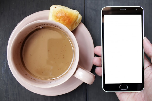 Hand, die smartphone mit braunem tasse kaffee auf schwarzem holztisch hält
