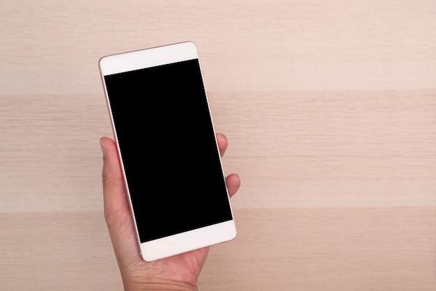 Hand, die smartphone mit dem leeren bildschirm lokalisiert auf hölzernem hintergrund hält
