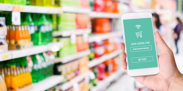 Hand, die smartphone mit lebensmittelgeschäfton-line-einkaufenanwendung hält