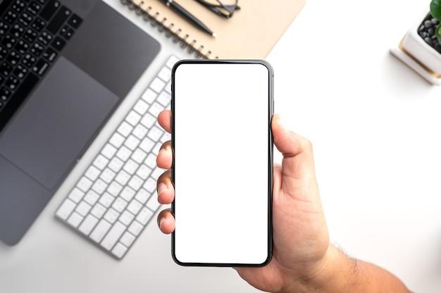 Hand, die smartphone mit weißem leerem bildschirm über desktop mit laptop-computer hält