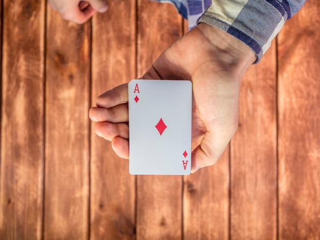 Hand, die spielkarten über der holzoberfläche mischt