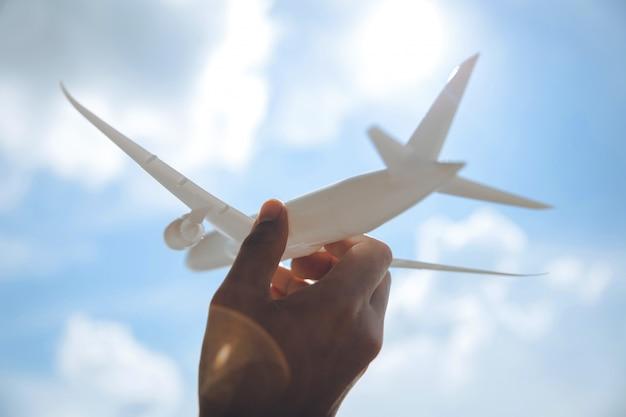 Hand, die spielzeugflugzeug gegen blauen himmel mit wolken hält. reiseinspirationsreiseflug.