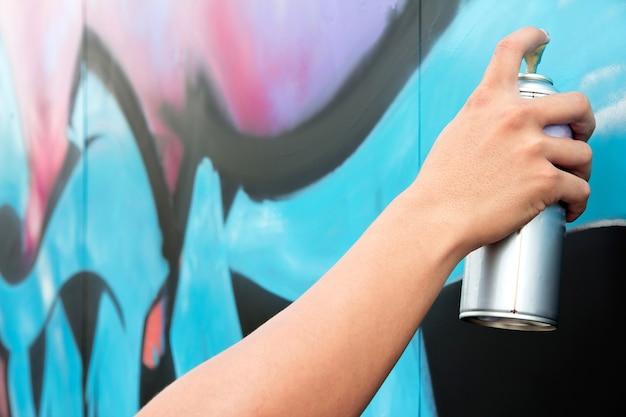 Hand, die sprühfarbe auf den wandgraffiti hält