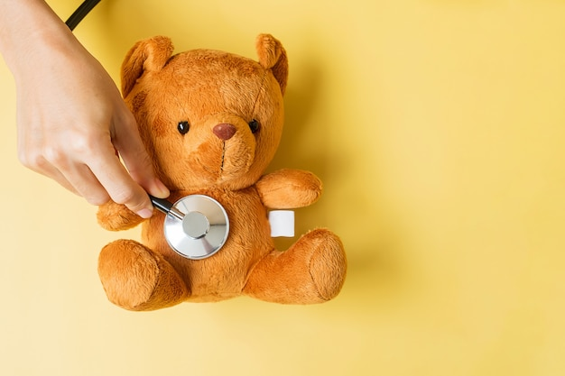 Hand, die stethoskop auf bärenpuppe hält, um das leben und die krankheit von kindern zu unterstützen. september aufklärungsmonat für kinderkrebs, gesundheits- und lebensversicherungskonzept