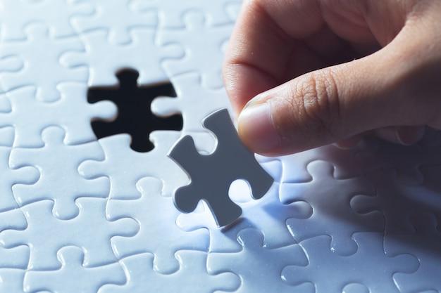 Hand, die stück des leeren puzzlen hält