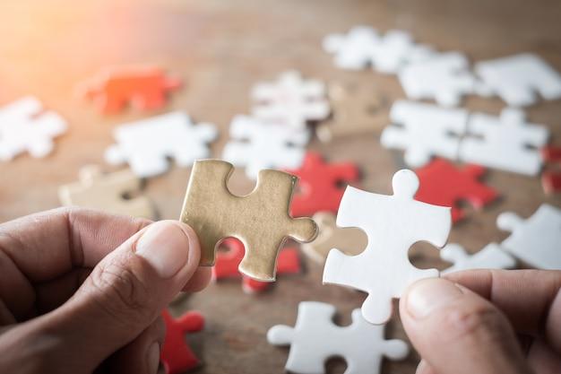 Hand, die stück des leeren puzzlespiels mit leerem puzzle auf holztisch hält