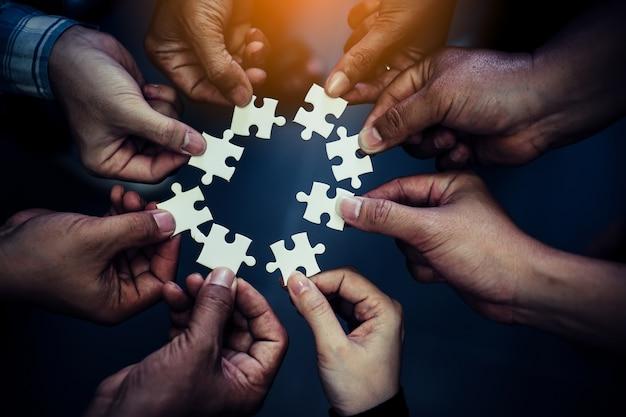 Hand, die stück des leeren puzzlespiels mit papierrahmenhintergrund hält.