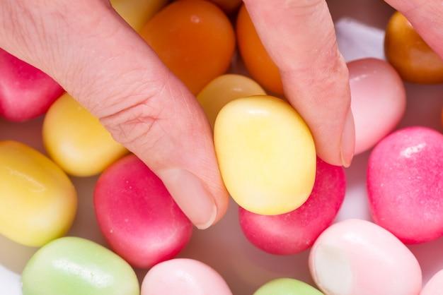 Hand, die süße süßigkeit auf farbigem hintergrund hält