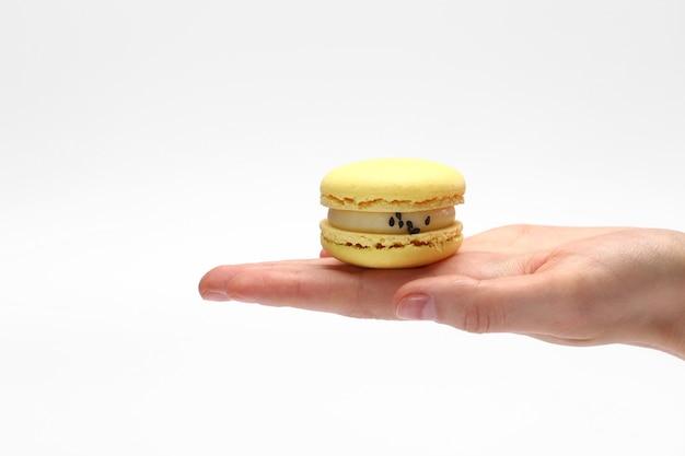 Hand, die süße und bunte französische gelbe makronen oder macaron lokalisiert auf weißem hintergrund hält.