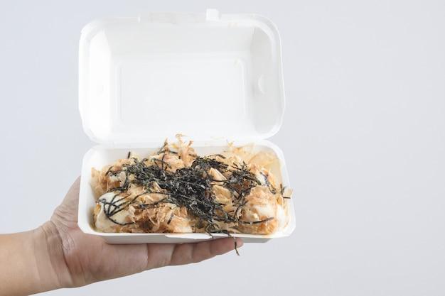 Hand, die takoyaki, einen mehlball hält, füllte mit krake, japanisches straßenlebensmittel