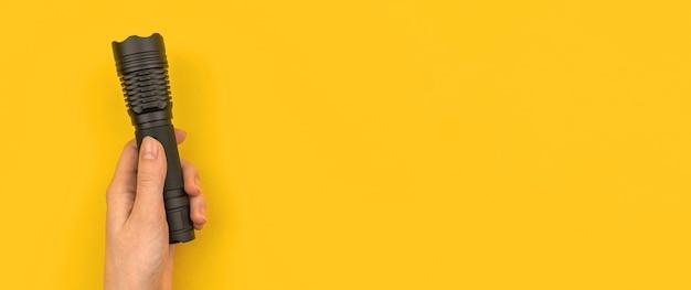 Hand, die taschenlampe auf gelbem schreibtischhintergrund hält, fahne mit kopienraumfoto