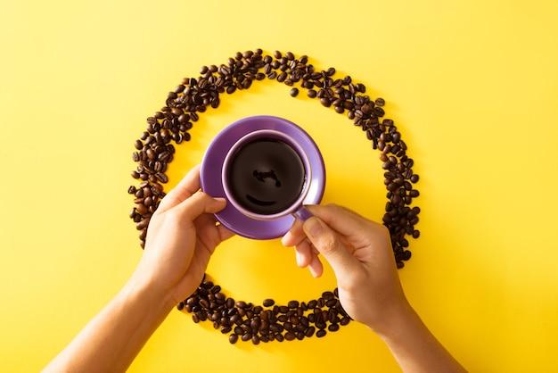 Hand, die tasse kaffee auf dem gelben hintergrund hält