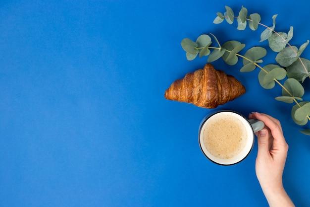Hand, die tasse kaffee, croissant und eukalyptusblätter auf blauem hintergrund hält.