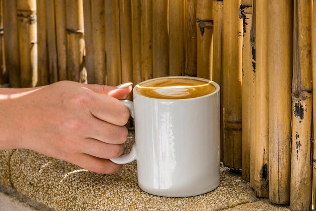 Hand, die tasse kaffee hält