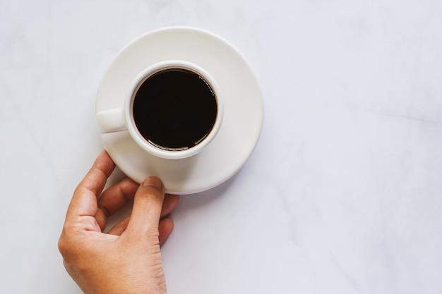 Hand, die tasse kaffee mit untertasse auf weißem marmorhintergrund hält