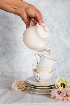 Hand, die teekannenatelieraufnahme hält